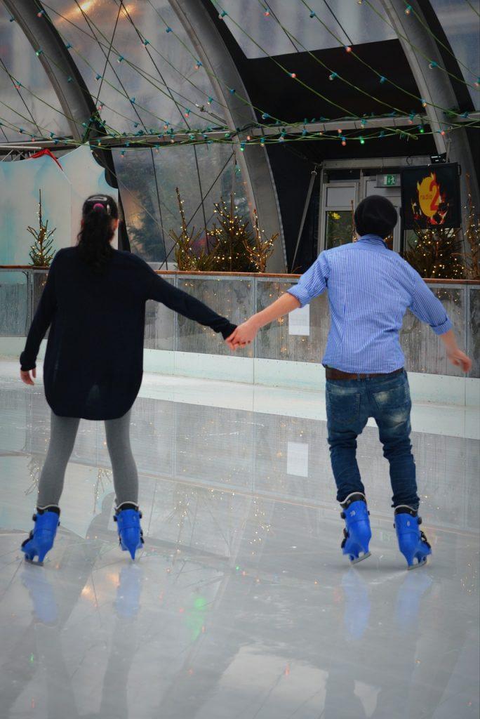 Girl and guy ice skating.