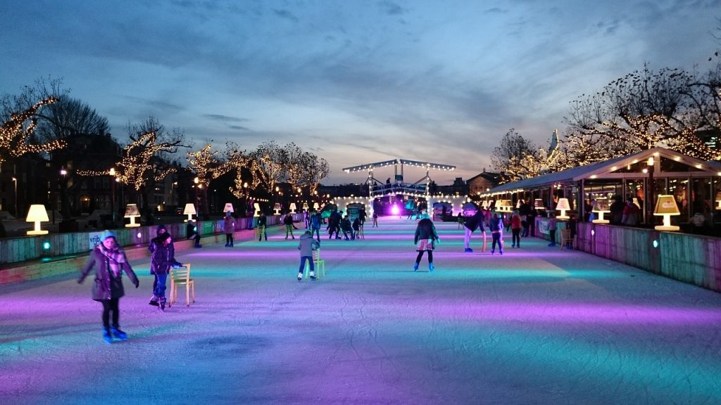 People ice skating at night at an outdoor rink.