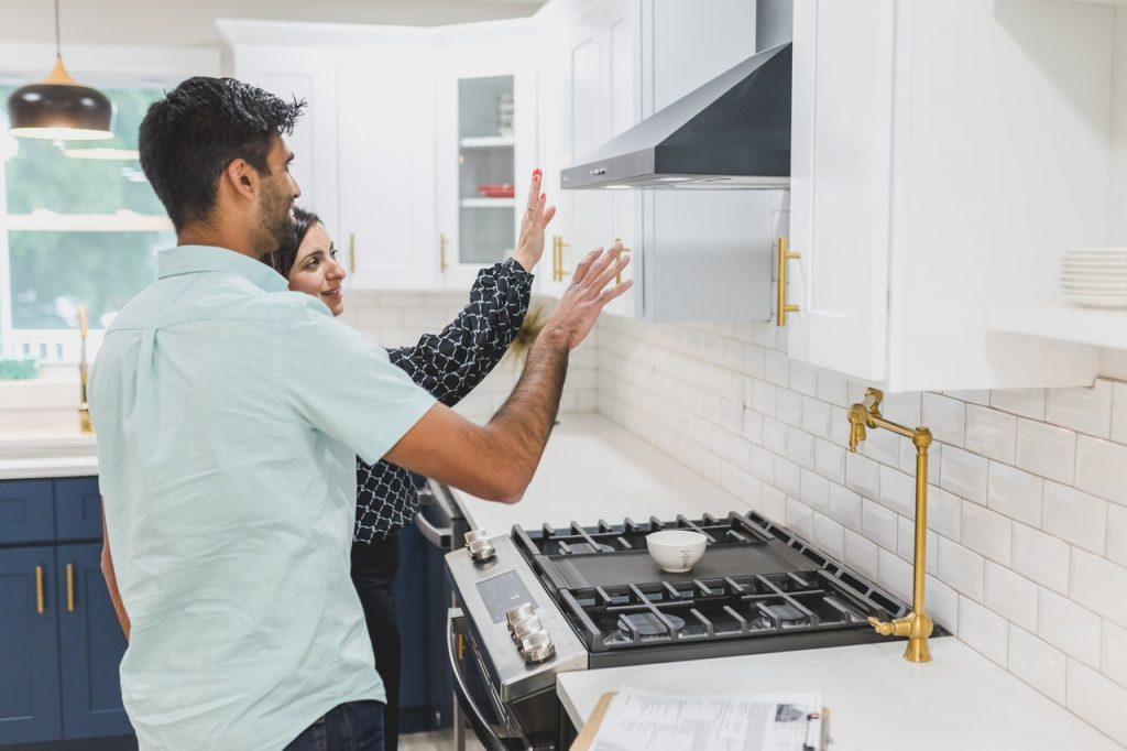 Guy and girl on a house hunting date looking at a kitchen.